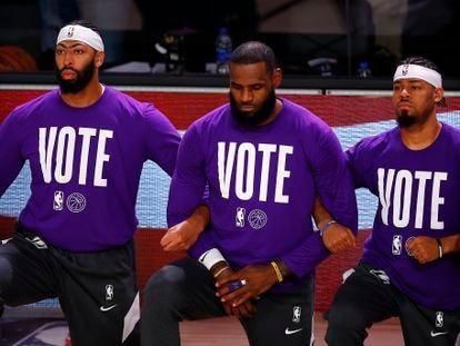 """Anthony Davis, LeBron James y Quinn Cook, de los Lakers, con el lema """"Vota"""" en sus camisetas."""