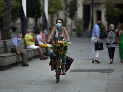 Una mujer con mascarilla pasea en bicicleta por el centro de Sevilla a principios de septiembre.