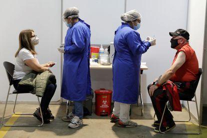Dos personas reciben la vacuna contra la covid-19, el 15 de junio, en el centro de vacunación más grande del Colombia, en Bogotá.