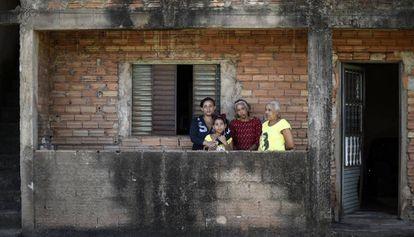 La familia Anunciação, ante su casa, en Congonhas. Solo una colina las separa de una balsa.