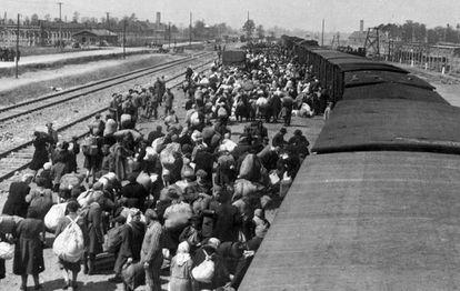Llegada de deportados a Auschwitz. Al fondo, las chimeneas de los hornos crematorios.