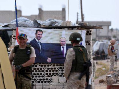 Militares rusos en un 'checkpoint' con un póster de El Asad y Putin, en el oeste de Siria.