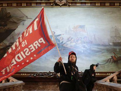 Un hombre lleva una bandera de apoyo a Trump durante el asalto al Capitolio en Washington, el 6 de enero.