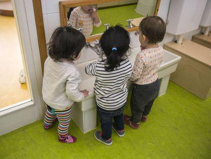 Tres niños, de espaldas, se lavan la manos en la guarderia Els Tres Tombs de Barcelona.
