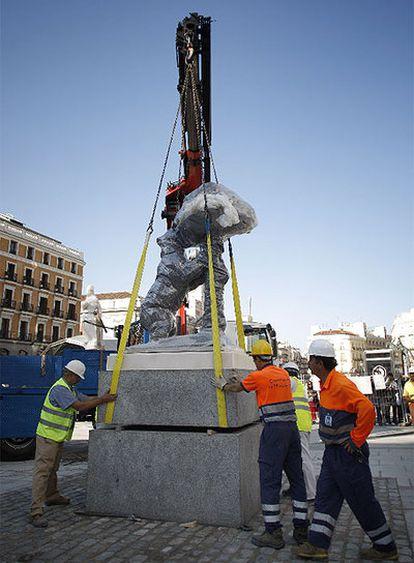 Unos operarios instalan la estatua del Oso y el Madroño, anteriormente ubicada en la calle del Carmen, en su nueva ubicación en la confluencia de Carrera de San Jerónimo y Alcalá.