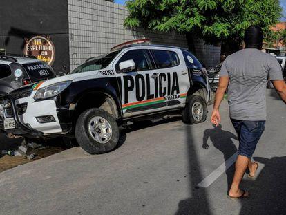 Un encapuchado, supuestamente policía, junto a una patrulla dañada al comienzo de la huelga.