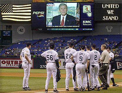 Los jugadores del equipo de béisbol de Tampa siguen la intervención de George W. Bush antes del inicio del partido.