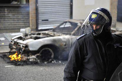 Un policía antidisturbio, frente a un vehículo quemado en Hackney, al este de Londres, durante el tercer día de disturbios.