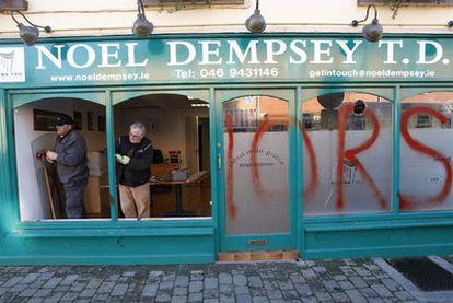 """Dos trabajadores reparan la cristalera de una oficina del Ministerio de Transportes en la localidad de Trim, asaltada y pintada con la palabra """"Traidores""""."""