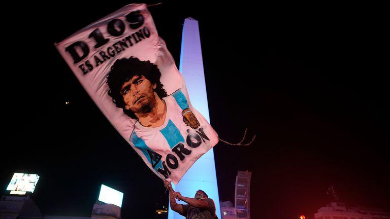 Un hombre ondea una bandera con el rostro de Maradona, en Buenos Aires.