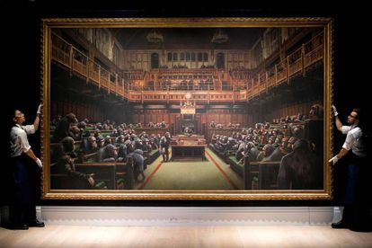 Two Sotheby's workers show the painting 'Devolved Parliament' to auction goers.