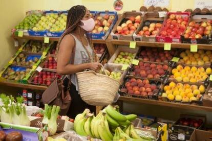 Una mujer con mascarilla, en una frutería de Madrid.
