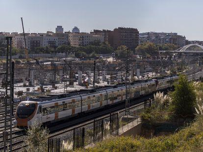 Un tren de cercanías pasa junto a las obras de la estación del AVE de Sagrera en Barcelona.