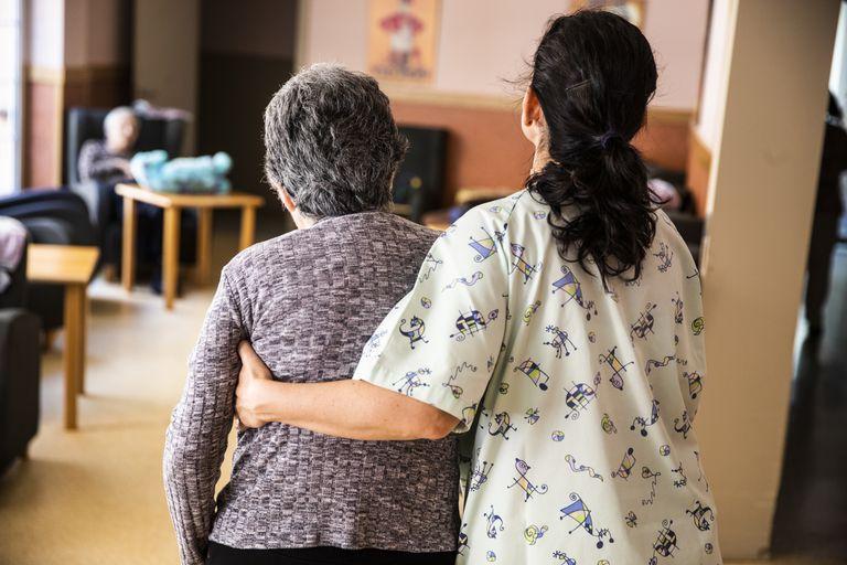 Una auxiliar ayuda a una mujer en una residencia de ancianos, en una foto de archivo.