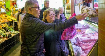 Una pareja hace la compra en un mercado de Sevilla.