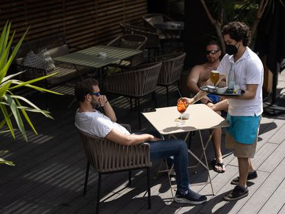 Un camarero sirve unas bebidas a clientes de un hotel de Barcelona.