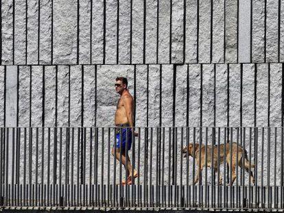 Un hombre pasea con su perro por Madrid Rio durante la ola de calor.