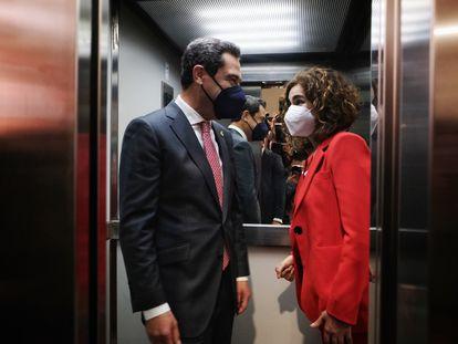 El presidente de la Junta de Andalucía, Juan Manuel Moreno, comparte ascensor con la ministra de Hacienda, María Jesús Montero, en la sede de CC OO en Sevilla.
