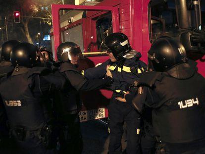 Manifestación en Madrid en apoyo al barrio de Gamonal en Burgos, donde desde el pasado viernes los vecinos han protestado incansablemente en contra del bulevar que el Ayuntamiento quiere construir en la calle de Vitoria. En la imagen, un bombero es detenido por la policía durante la manifestación.