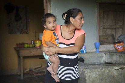 Edis esposa de Manuel sujeta en brazos a su nieto Anthony en su pequeña casa en Honduras.