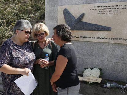 La presidenta de la Asociación de Afectados, Pilar Vera (i), conversa con dos mujeres en la ofrenda floral en Madrid.