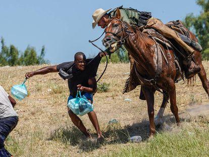 Un agente a caballo de la Patrulla Fronteriza de Estados Unidos intenta evitar que un migrante haitiano llegue al campamento a orillas del río Grande cerca del puente que une Texas y México.