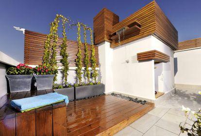 Ático en Madrid con cortavientos de madera termotratada que permite su uso todo el año, de Un Jardín Para Mí.