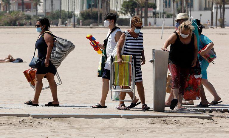 Varias personas protegidas con mascarillas acceden a la playa de la Malvarrosa de Valencia.