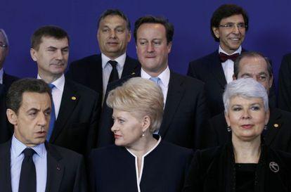 David Cameron (centro) mira a Nicolas Sarkozy durante la foto de familia de la cumbre europea.