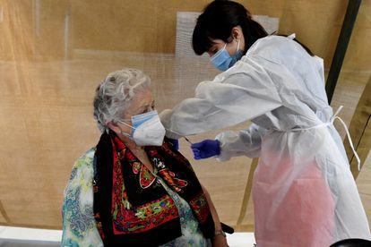 Una empleada sanitaria inocula una dosis de la vacuna contra la covid-19 durante la jornada de vacunación masiva a mayores de 80 años que se realiza este jueves 1 de abril de 2021 en el Palacio de Congresos de León.