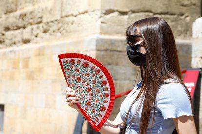 Una mujer se abanica mientras pasea por el centro de Córdoba.