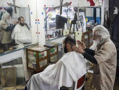 El peluquero don Manuel con un cliente.