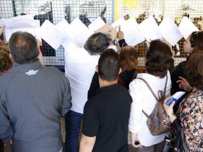 Un grupo de personas busca su mesa en las listas del censo electoral en el Ministerio de Educación. En vídeo: declaraciones de votantes de Olivenza, Badajoz.