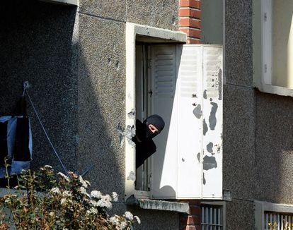 Un policía mira por la ventana del edificio asaltado.