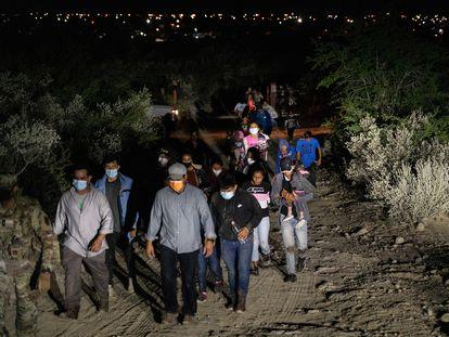 Solicitantes de asilo son escoltados por agentes estadounidenses tras cruzar el río Bravo, en la frontera con México.
