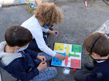 Tres niños juegan al parchís sobre el asfalto.