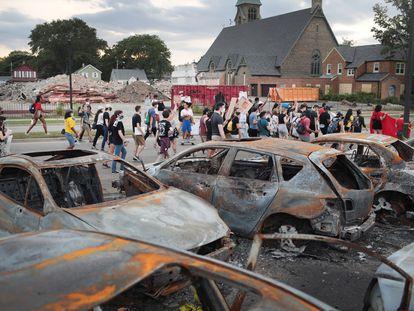 Un grupo de manifestantes pacíficos pasa junto a unos coches quemados en Kenosha.