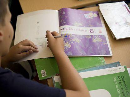 Imagen de archivo de un alumno con un libro de Religión.
