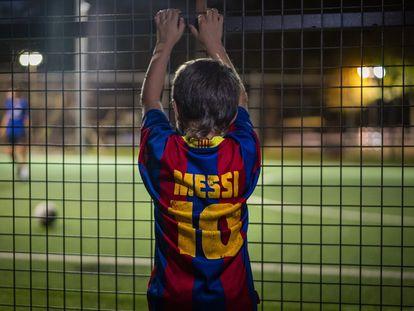 Un niño con la camiseta de Messi observa un partido en Girona a través de una valla.
