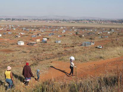 Una familia camina hacia una zona de asentamiento informal en Sudáfrica.