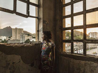 Mulher em frente às janelas do edifício abandonado do Ministério da Fazenda na favela da Mangueira, situada na zona norte do Rio de Janeiro, a menos de um quilômetro do estádio do Maracanã, epicentro da Copa do Mundo de futebol e dos Jogos Olímpicos do Rio de Janeiro.