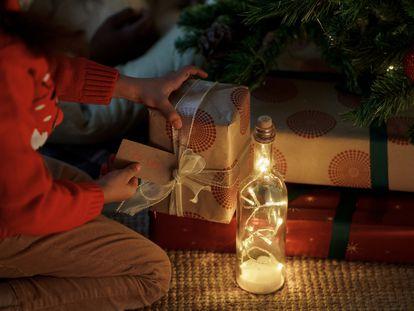 Un niño busca su nombre entre los regalos que han dejado los Reyes Magos bajo el árbol.