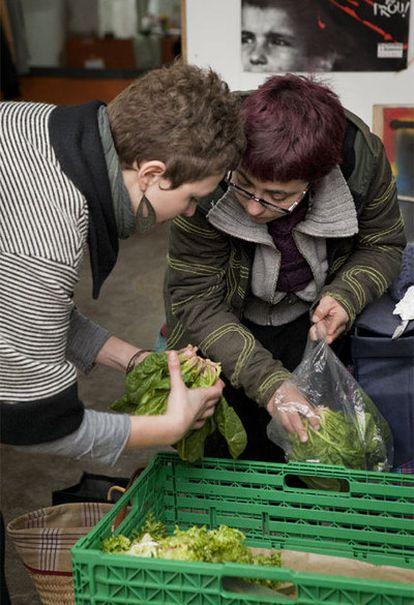 Dos mujeres cogen verdura en una cooperativa del barrio del Clot.