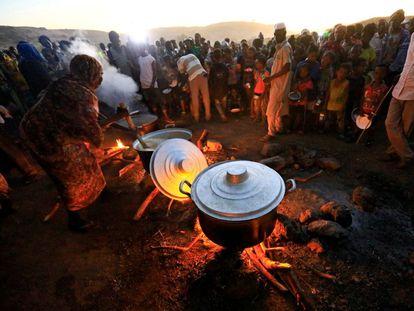 Refugiados etíopes que huyen de la guerra en Tigray esperan a recibir comida en el campo de refugiados sudanés de Um-Rakoba, cerca de la frontera entre ambos países, el pasado lunes.