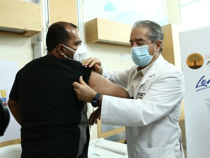 El ministro de Salud de Ecuador, Juan Carlos Zevallos, explica con un voluntario el proceso de vacunación contra la covid-19, el 21 de enero en Guayaquil, Ecuador.