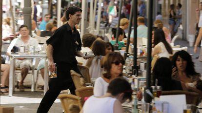 Un camarero trabaja en una terraza en Valencia.