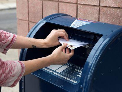 Una persona deposita cartas en un buzón del servicio postal en Filadelfia (Pensilvania) el 14 de agosto.