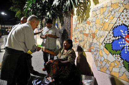 Voluntarios de San Egidio reparten alimentos y bebida entre personas en situación de calle en Flores.