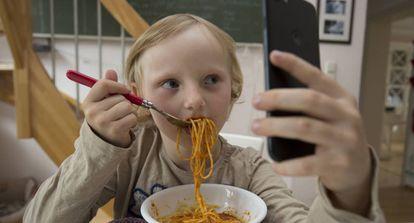 Ver dibujos en el móvil durante la comida, una práctica cada vez más habitual entre los niños.