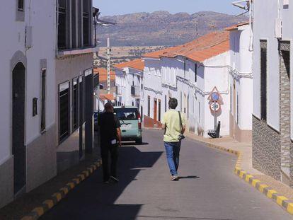 Dos personas caminan por una calle de Puerto Hurraco (Badajoz).